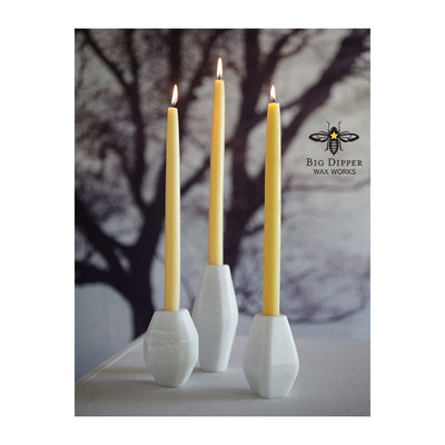 three natural colored 100% Pure Beeswax tapers in white ceramic holders, with winter tree backdrop