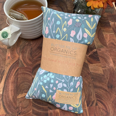 floral blue hot and cold pack made with organic flax seed and lavender. Measures 5 X 9 inches. displayed next to brewed tea in ceramic mug