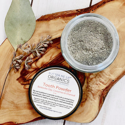 grey tooth powder in glass container, 2 oz, displayed on knotted wood