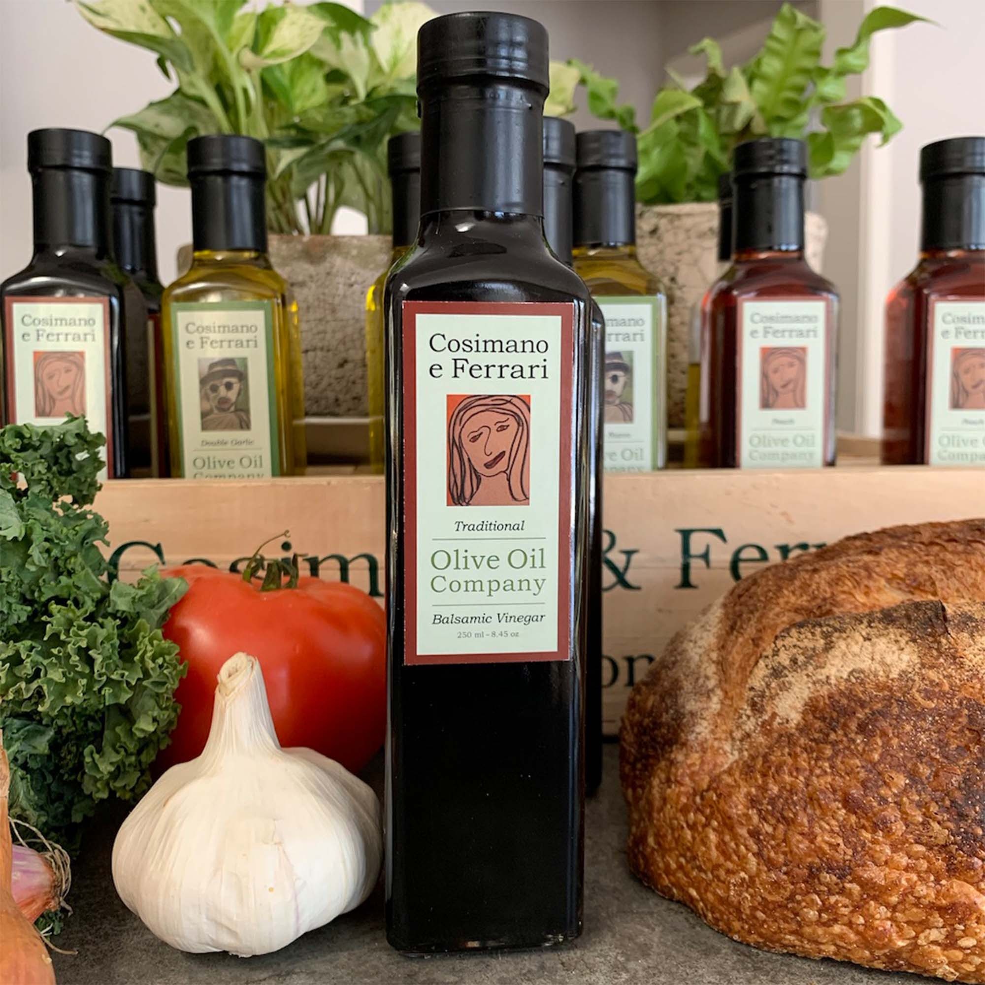 garlic, kale, tomato and sourdough bread surrounding tall bottle of olive oil with graphic of smiling women on front.