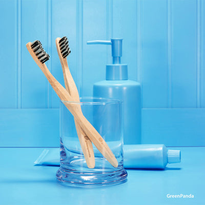2 Adult size, plastic free bamboo toothbrushes with plant based bristles in blue glass. blue monochromatic bathroom