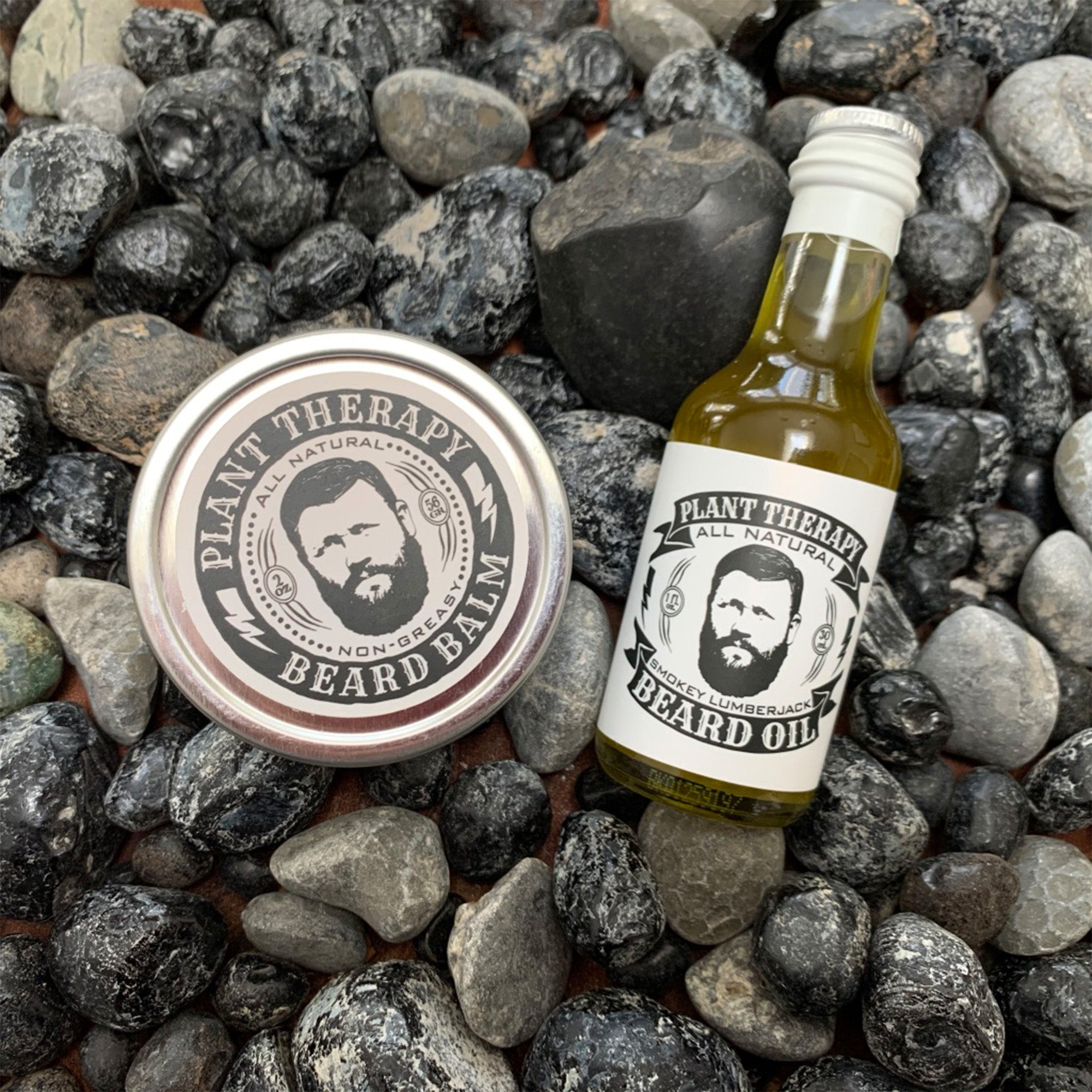 beard balm circular tin, with beard oil bottle, sealed. placed on assorted rocks