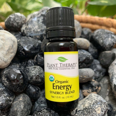 10 ml black bottle with yellow label. organic energy synergy essential oil blend. displayed on assorted rocks