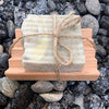 bar soap, European clay and avocado full size on wood coaster wrapped in twine, displayed on rocks