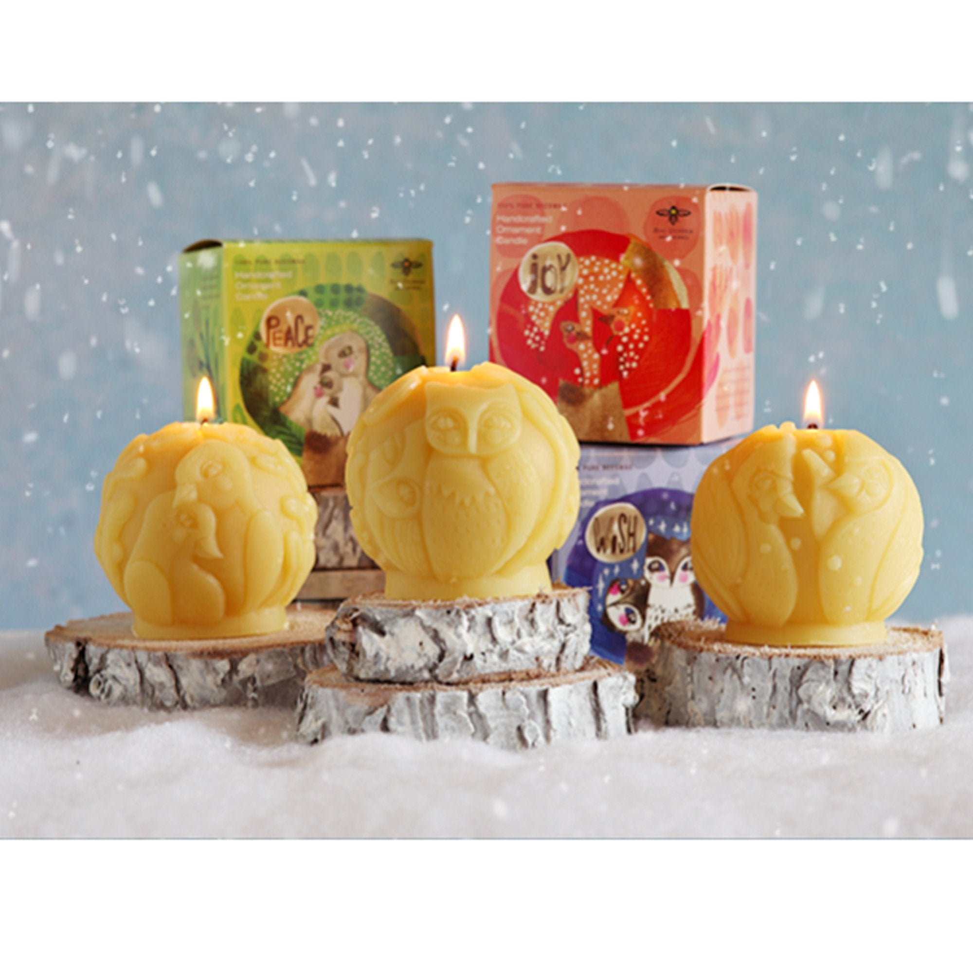 three sculpted naturally colored beeswax candles and three packages set in snowy environment. designs include doves, owls, cardinals.