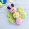 knitted pink and green baby rattle shaped like a smiling butterfly