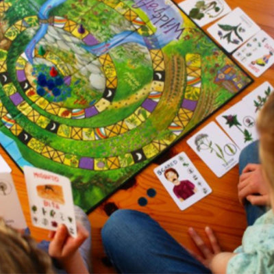 two children playing wildcraft board game with cards surrounding game board