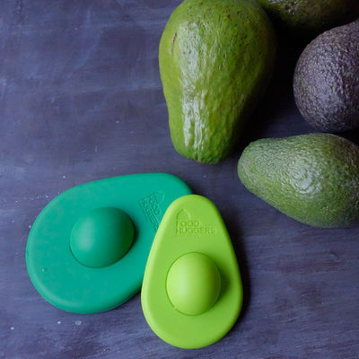 2 reusable green silicone avocado savers, one small and light green, one large and dark green, next to 3 ripe avacodos