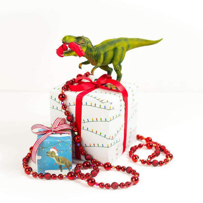 two packages wrapped in TRex and string light paper, with a toy dinosaur on top