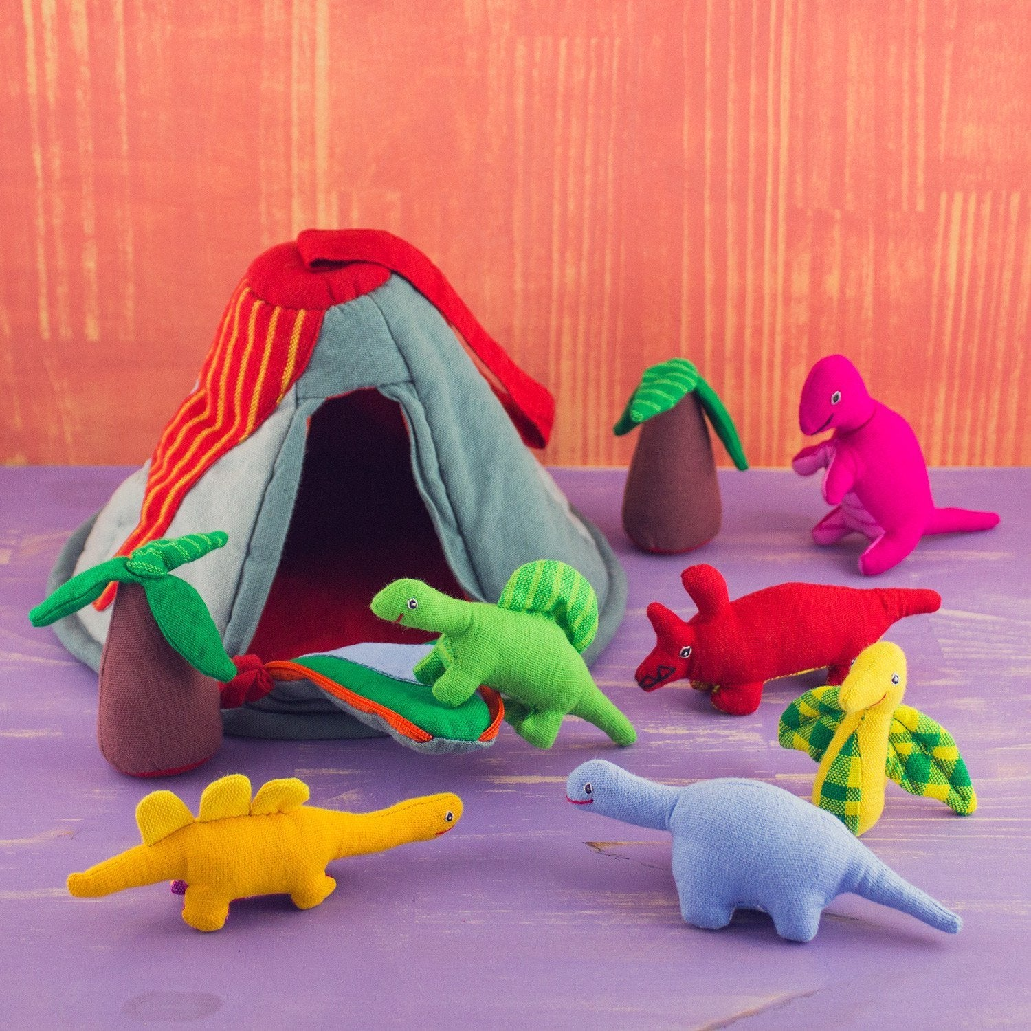 6 soft happy dinosaur toys, two soft palm tree toys, and a soft volcano toy. multicolored