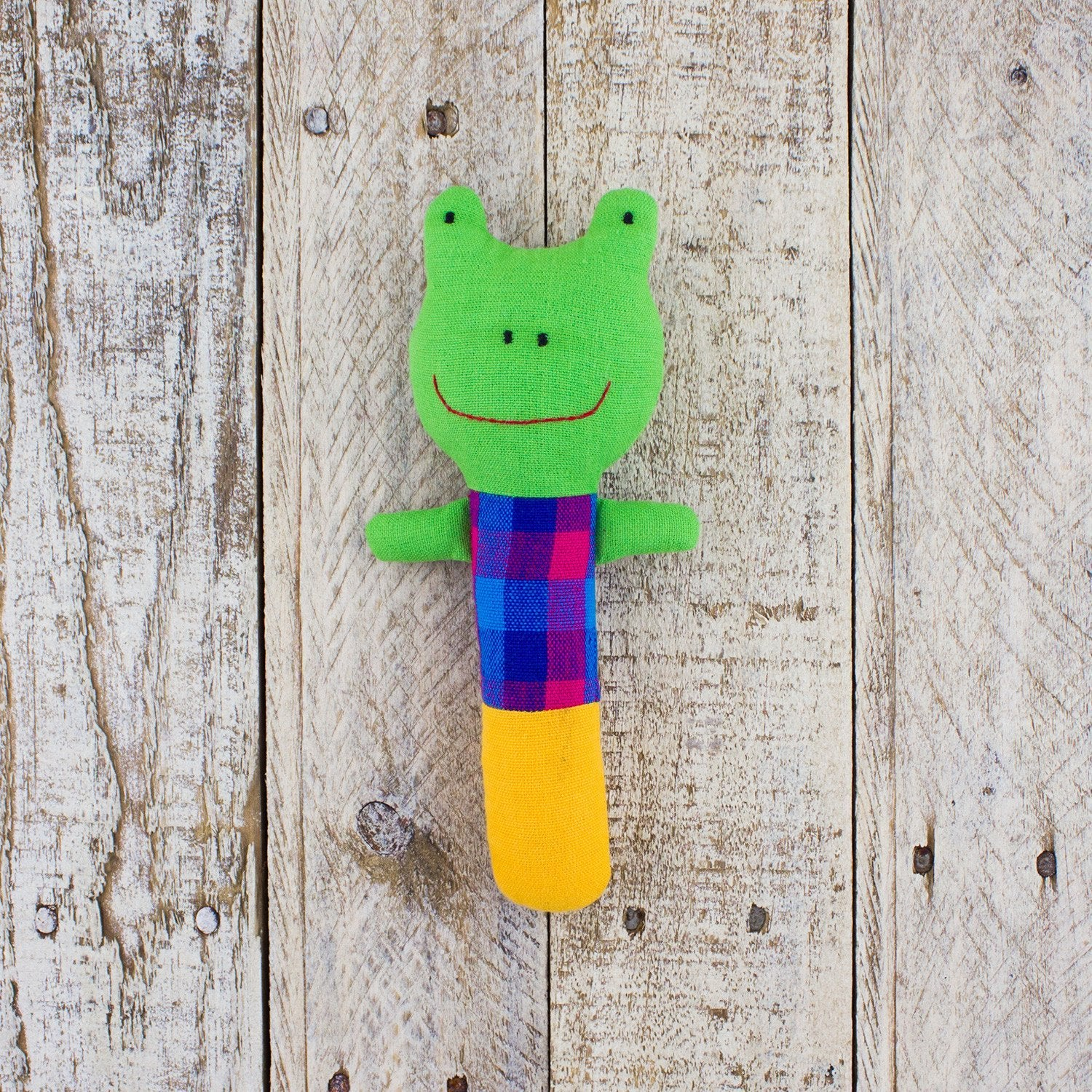 smiling frog shaped baby rattle with plaid shirt design on reclaimed wood tabletop