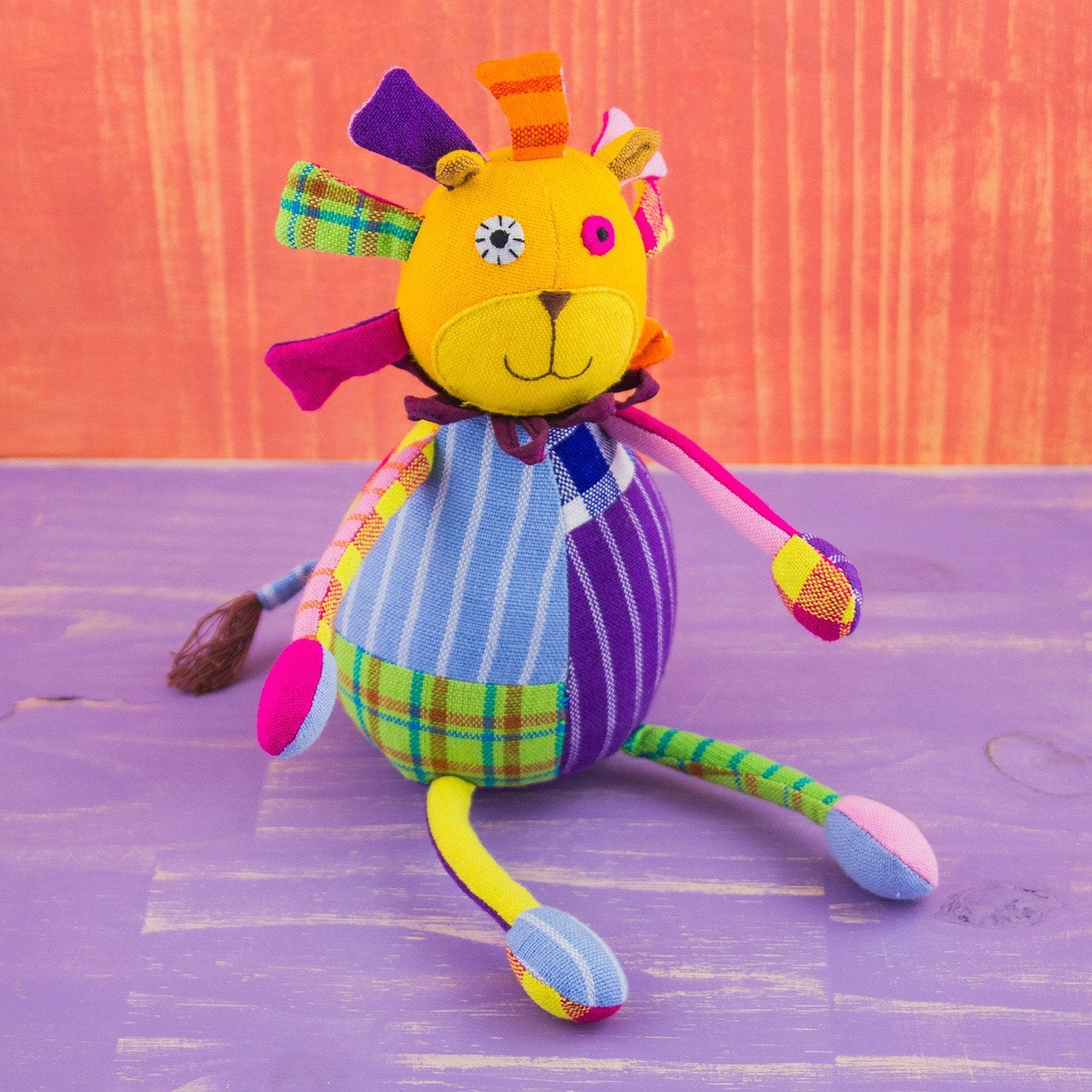 soft lion shaped doll, lion is constructed of quilt like patches, giving it many colors and patterns