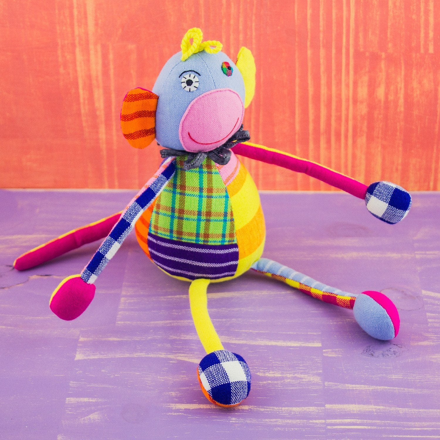 soft monkey shaped doll , monkey  is constructed of quilt like patches, giving it many colors and patterns