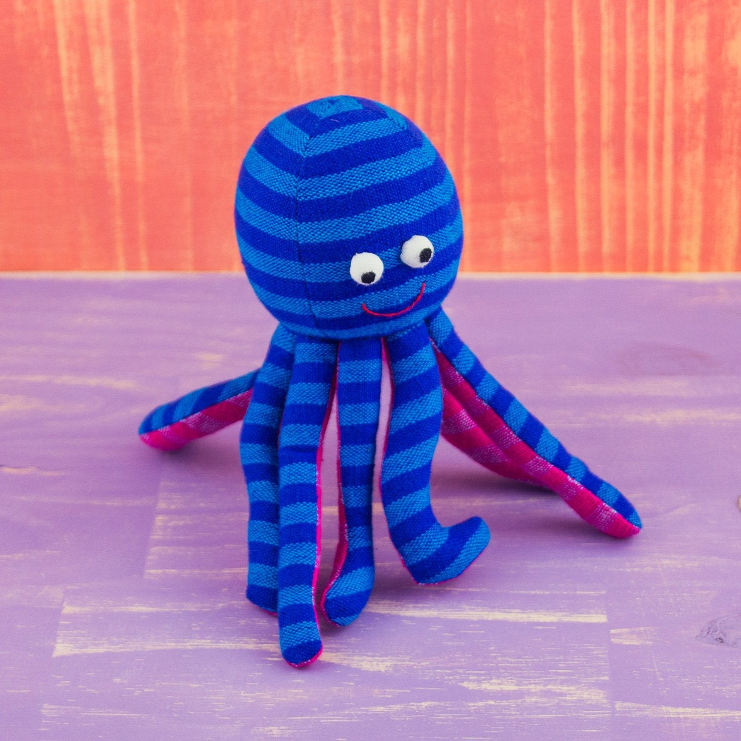 blue striped outside, pink striped underside googly eyed, octopus shaped doll