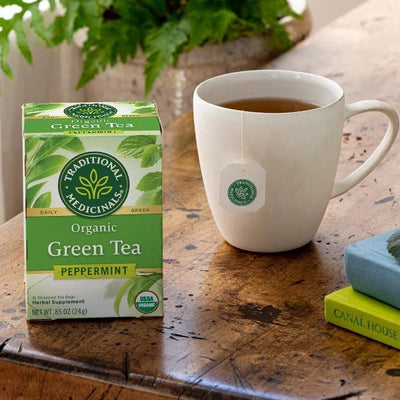 Organic Green Tea Peppermint by Traditional Medicinals®, net wt .85 oz, 16 wrapped tea bags, on wood table next to ceramic mug with brewed tea and tea tag