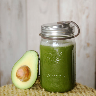 avacado slice resting on mason jar filled with green juice, includes eco jars lid and brown pop top
