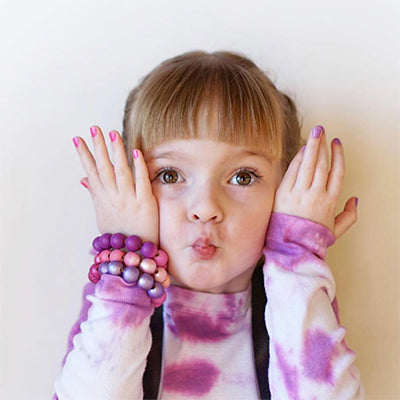young girl with purple shirt and purple braclets showing pink/purple nails while making silly face