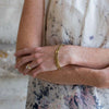 freckled women with large engagement ring and floral blouse with golden seed + barrel bracelet on left wrist, arms crossed