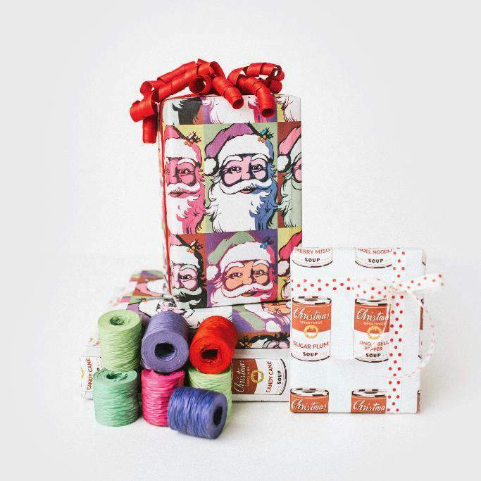 two packages wrapped in Warhol paper next to spools of ribbons.