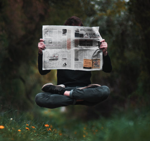man floating holding a newspaper in the woods
