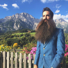 Madison Rowley stands wearing a blue suit and his World Champion Beard in front of Austrian Alps