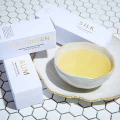 Body Oils in white cartons with oil filled bowl in center