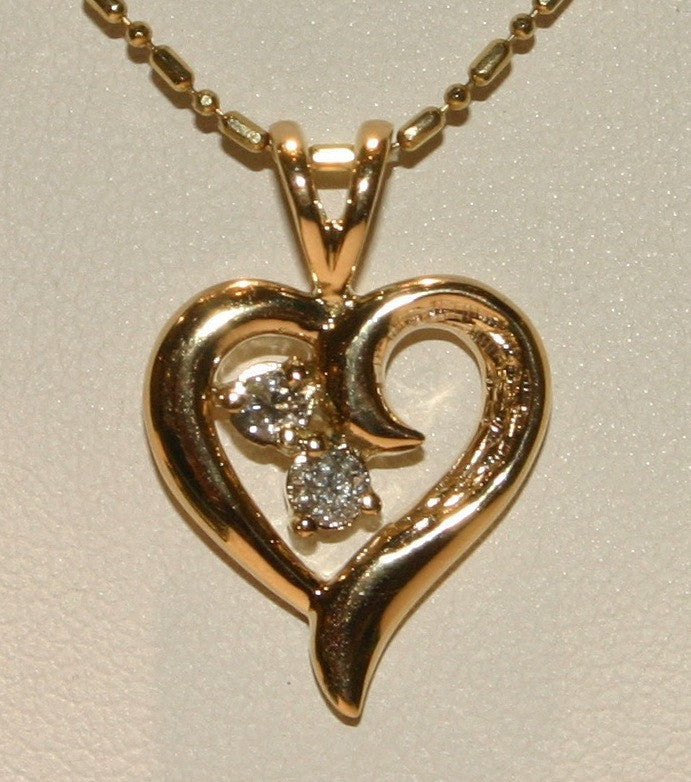 gold heart pendant with two diamonds