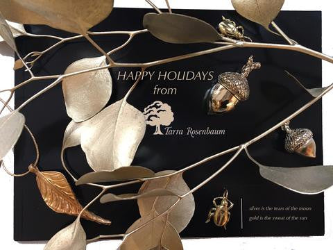 black and gold happy holiday announcement with gold charms of scarabs and acorns