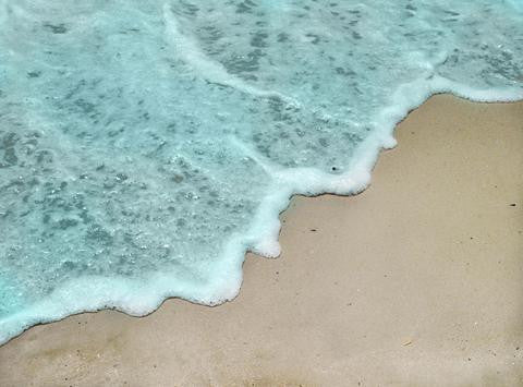 Photo of the blue ocean coming up on the beach