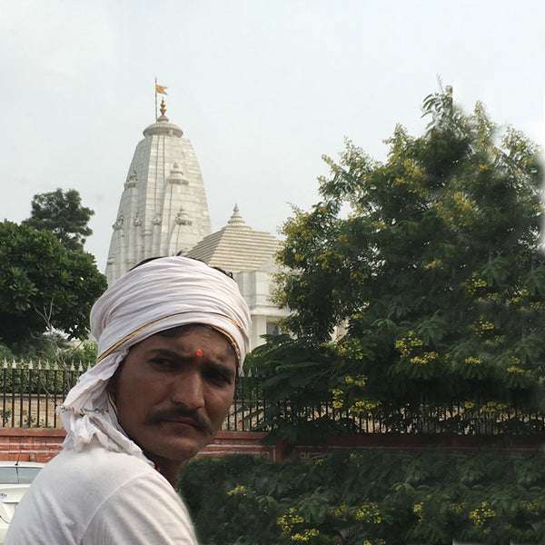 A man looking at you with a wrap on the head with a temple in the background