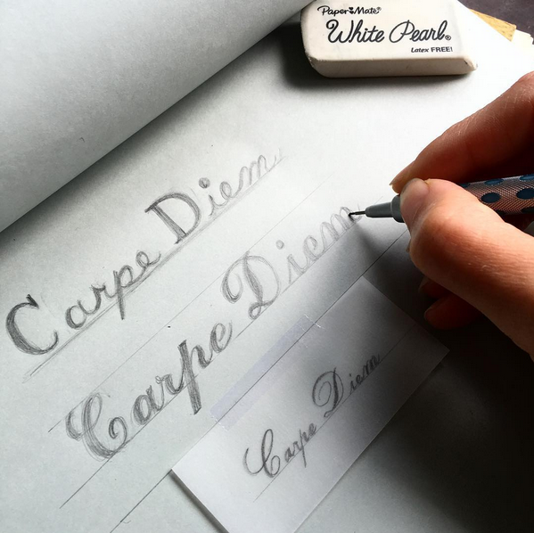 a hand writing out carpe diem in different fonts for engraving
