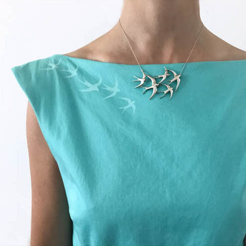 A necklace of a flock of five sterling silver swallow hangs against a turquoise boat neck dress that has silk screened swallows that fly into the necklace.