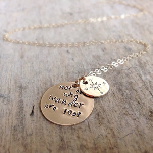 Close up of 14K Yellow Gold Compass Charm Necklace on table