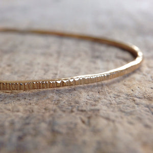 Close up of 14k gold filled tree bark bangle on table