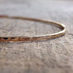 Close up of 14k gold bangle on table
