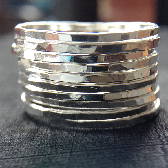 A stack of 10 silver stacking rings on a table