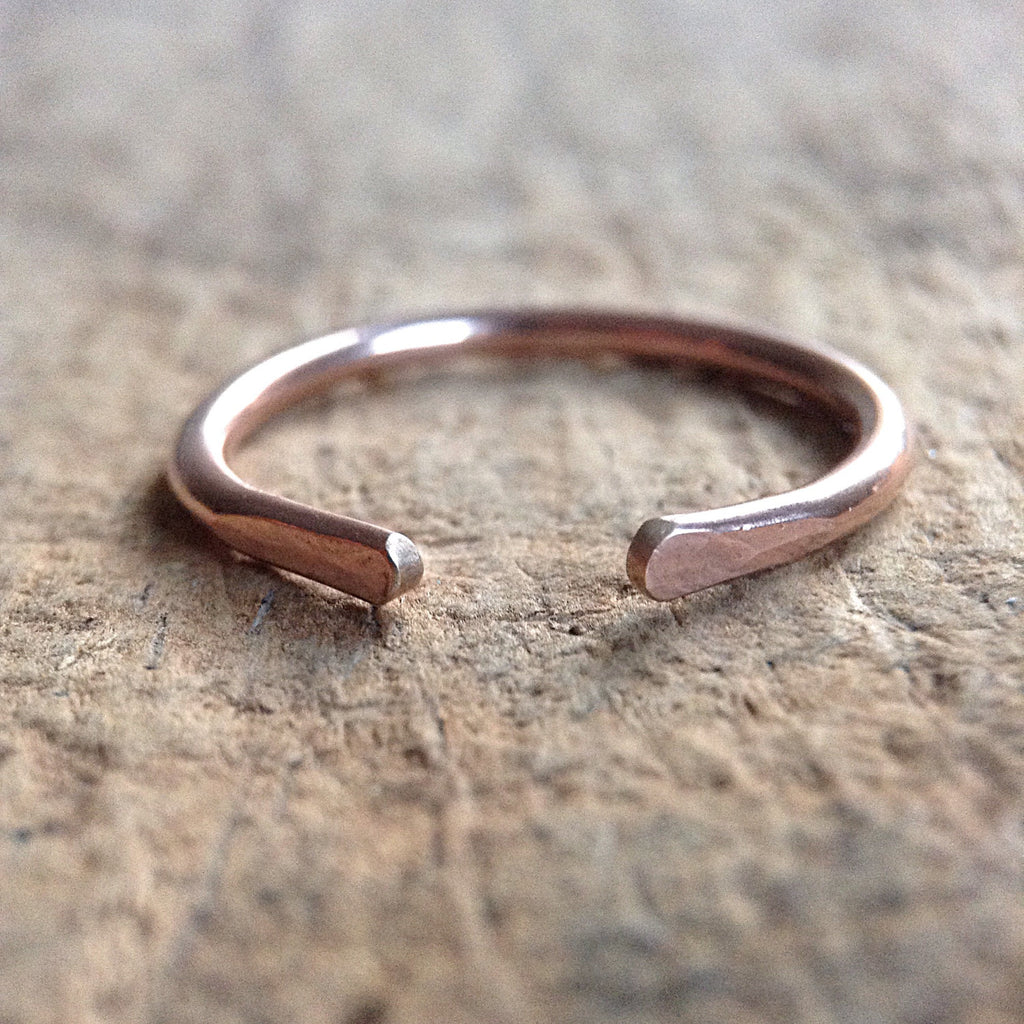 A single rose gold stacking ring on a table