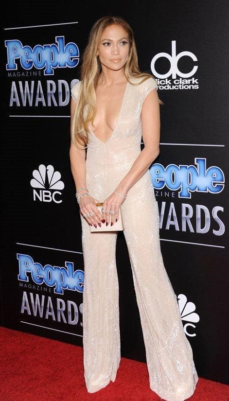 3503a65d898a Jennifer Lopez wore a Naeem Khan white and nude beaded jumpsuit with an  Elie Saab clutch