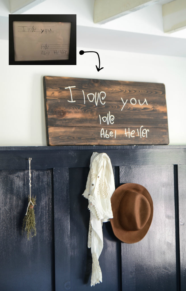 "Handwriting memory sign on wood above sweater and hat in mudroom ""i love you"""