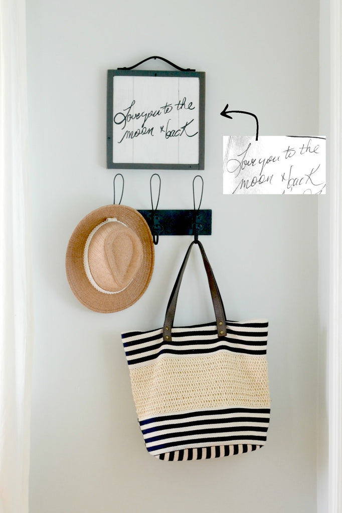 "Handwriting memory sign on wood ""Love you to the moon and back"" hanging above coat rack with hat and bag"