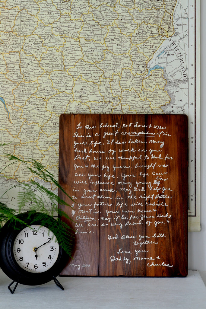 Handwriting memory sign on wood with map, clock and fern