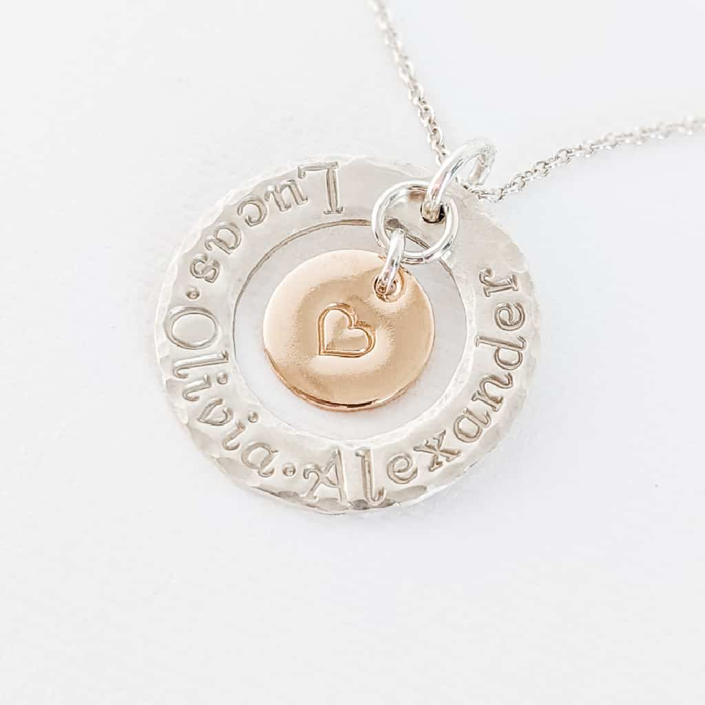 Sterling silver circle washer necklace with 1 2 3 kids names stamped around ring and gold fill heart disc hangs in the center - Mother's Day gift ideas for Mom or Grandmother