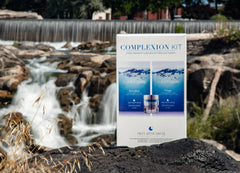 The Complexion Kit box sitting on rocks in front of a water fall.