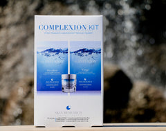 The Complexion Kit Skincare Routine Box sitting on a stone bench.