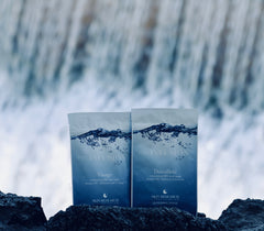 neuINFUSION™ Dry Sheet masks sitting in front of a waterfall.