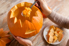 Pumpkin with its seeds being removed by a woman.