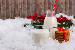 Gifts and milk set in snow with a wooden background.