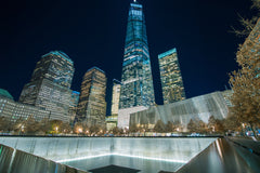 The new world trade center buildings standing in the background of the memorial.