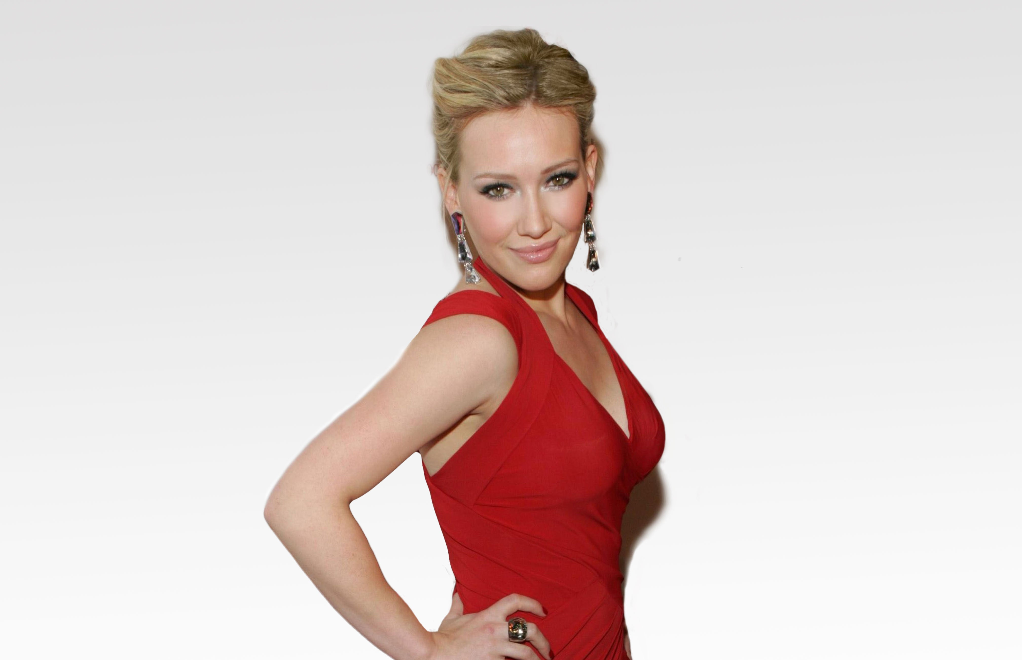 image of Hillary Duff wearing a red halter top dress posing in front of white back drop