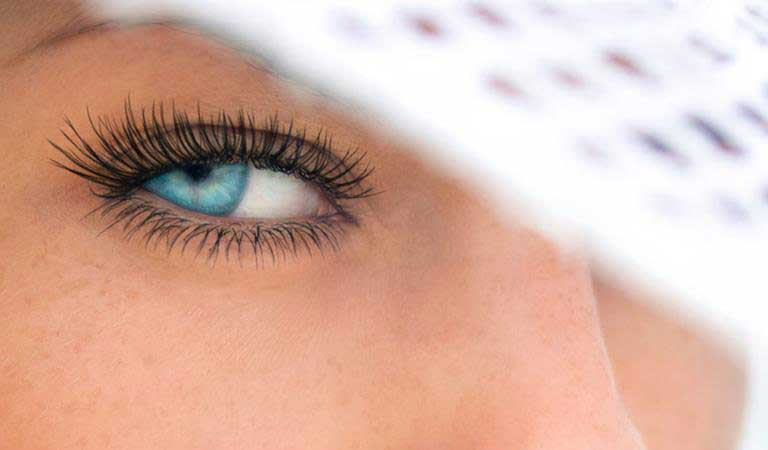 close up of woman gazing into camera with one eye and hat obscuring part of her face